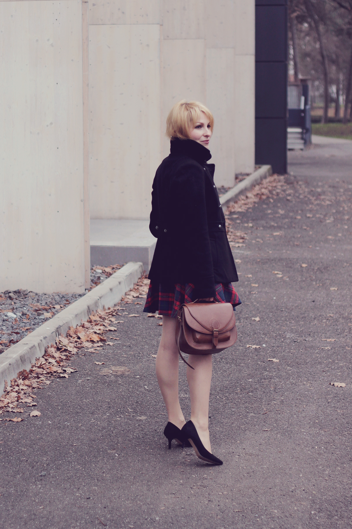 black heels and coat with brown handbag and tartan dress