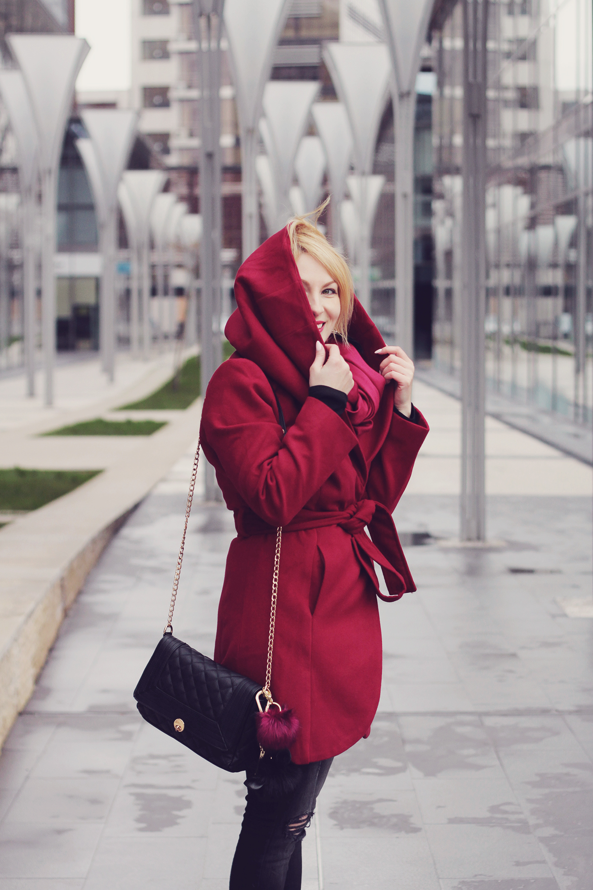 burgundy coat and black chain clutch with pom-poms