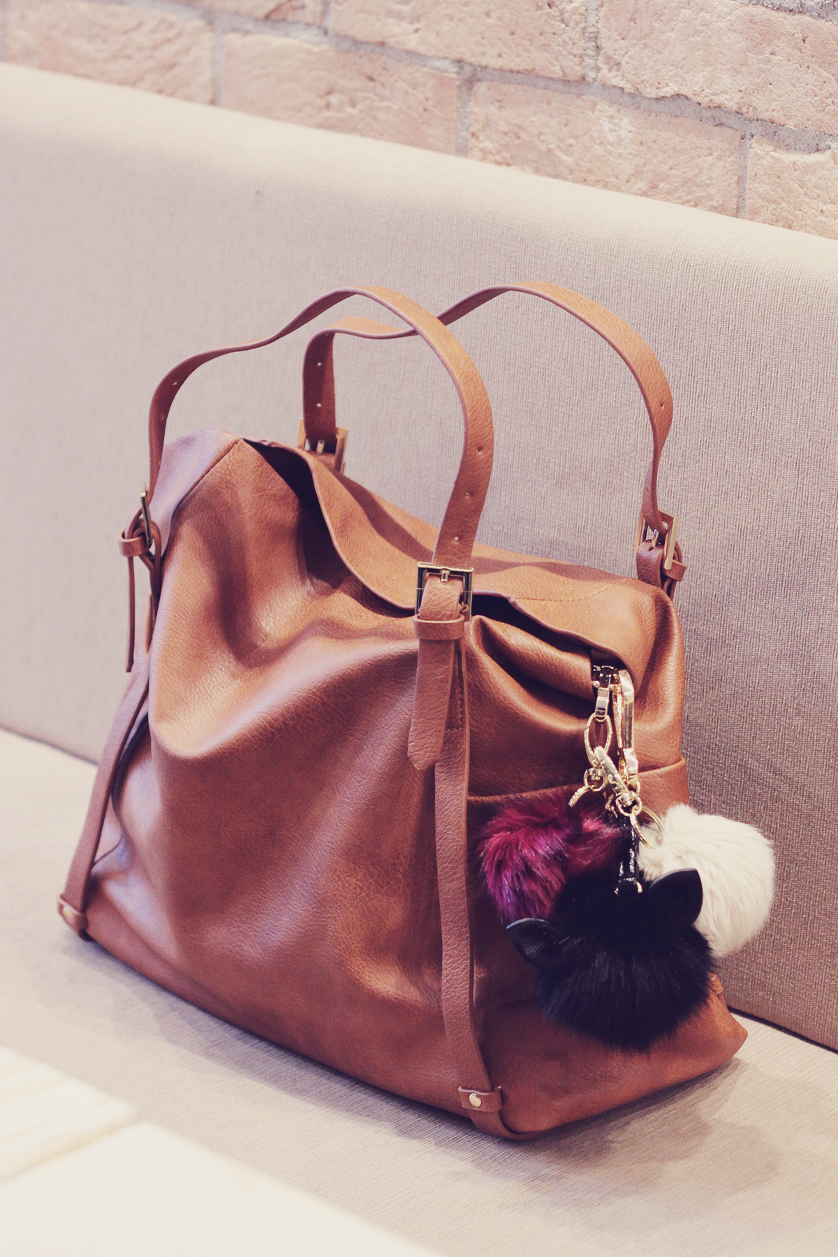 large brown tote bag with pom-poms