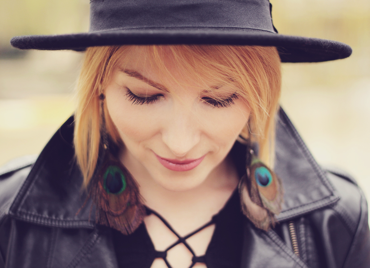 peacock earrings and wool hat