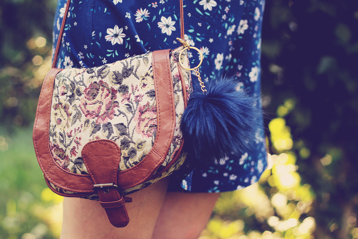blue pom-pom and floral purse