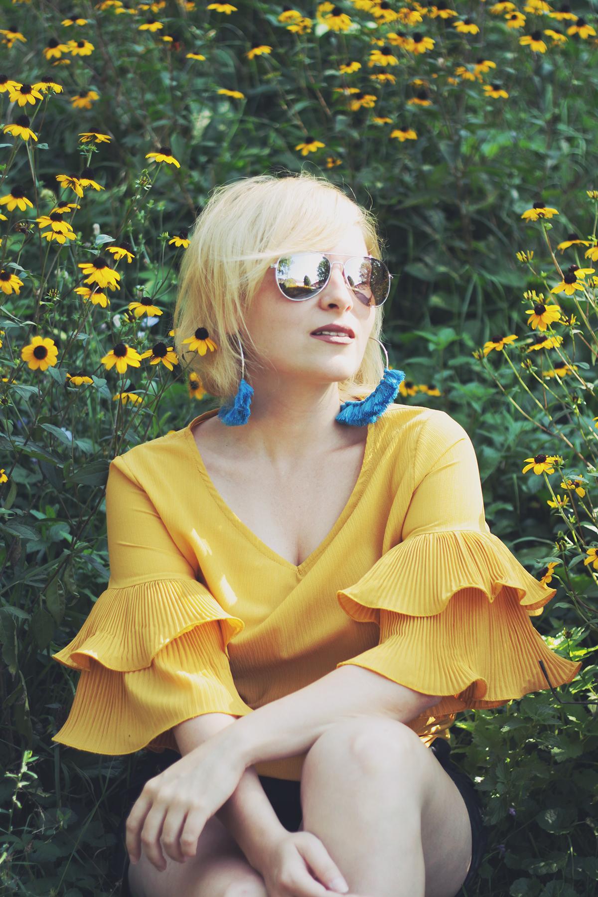 yellow ruffle top, blue tassel earrings, nature, yellow flowers