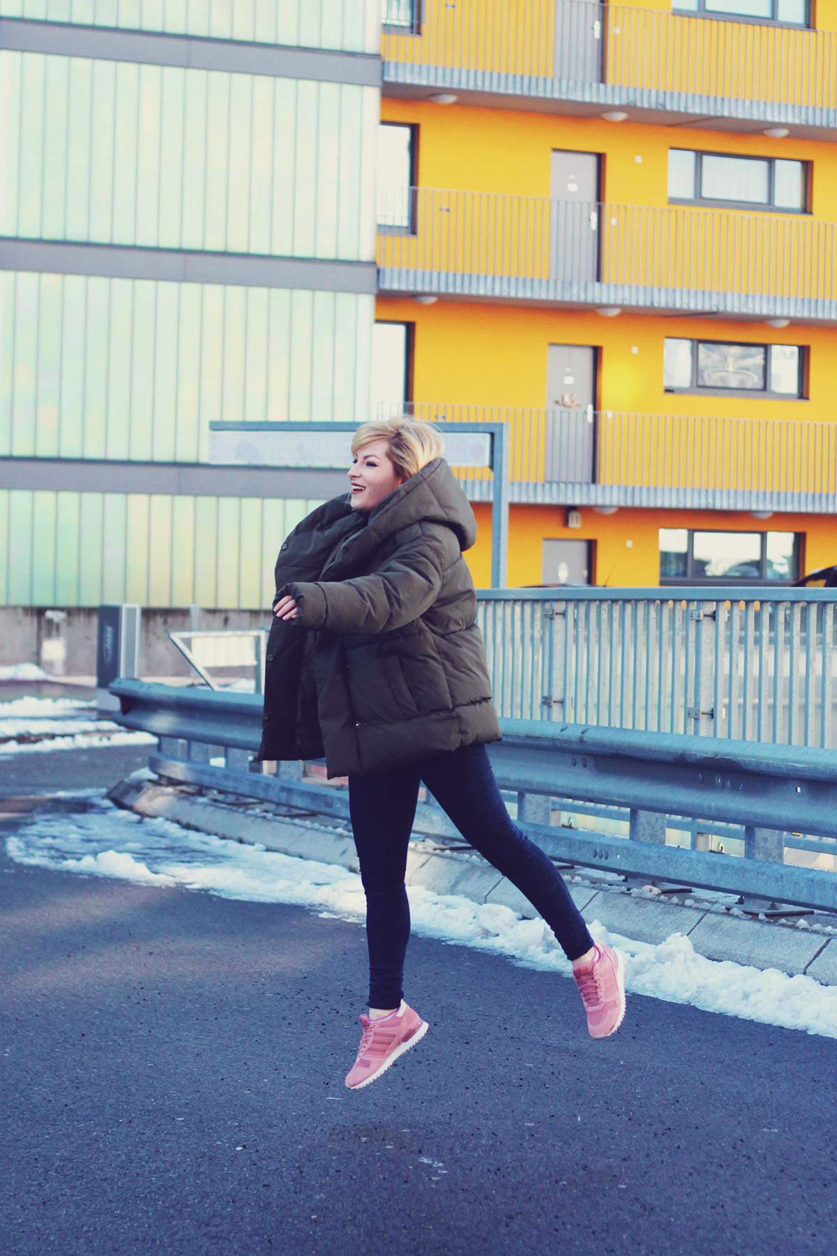 winter fashion, padded jacket, jeans, pink adidas originals, girl jumping, urban landscape, Vienna, snow